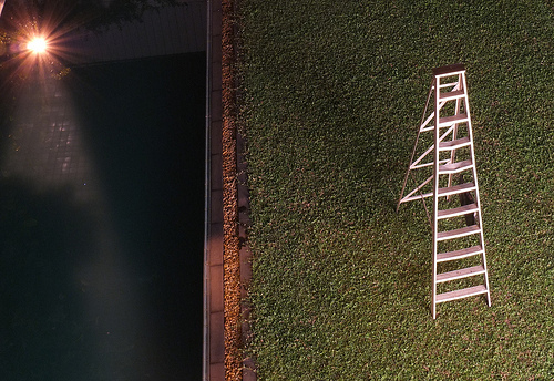 a white ladder in a field. Off to the left is a dark area with a point of light shining