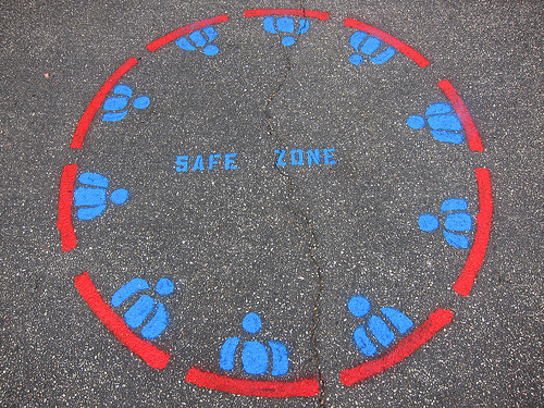 "A painting on a sidewalk of a red circle. (drawn with a dotted line) The edges of the circle are studded with chest-up simplified silohuettes of people painted in below. In the center of the circle the words ""safe zone"" are painted in blue letters."