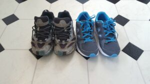 2 pairs of sneakers on a tile floor. the ones on the left are old and falling apart. the ones on the right are brand new.