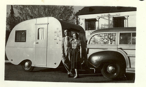 an old black and white photo of a couple standing in front of a car with a trailer attached, vintage travelers