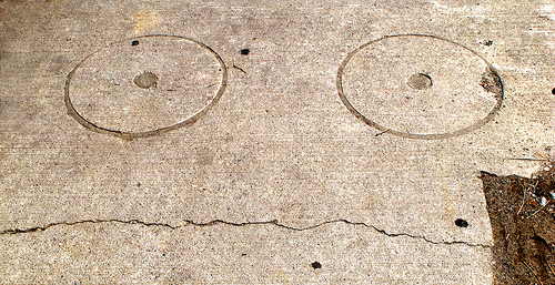 a very insecure and worried looking face carved into a sidewalk