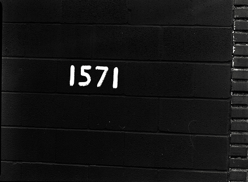 "a black stone wall with the white numbers ""1571"" painted on it as an address"