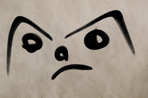 a very basic drawing of an angry face, made with a black marker