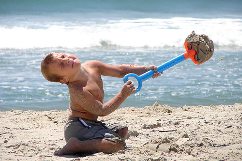 a young boy on a beach with a plastic shovel full of sand. his hand is thrown back and his eyes are closed as though he is trying very hard and expending a lot of effort