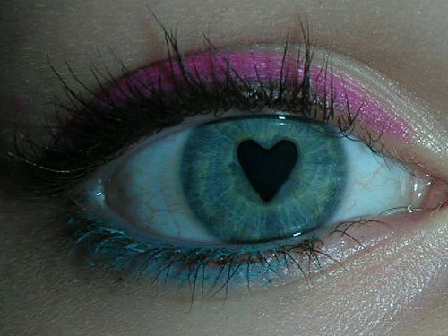 a close up of a hazel eye with a heart shaped pupil. The eyebrows have mascara. The upper eyelid has pink eyeliner. The bottom eyelid has blue eyeliner.