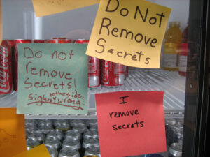 3 post it notes stuck to what seems to be a transparent break room fridge. the notes read starting at the top and moving clockwise: 1) Do not remove secrets 2) I remove secrets 3) Do not remove secrets! The sighn [sic] on the side is wrong.