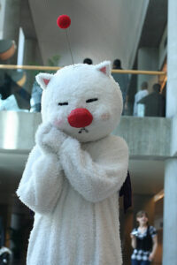 a person wearing a Moogle costume (from the Final Fantasy series). Moogles are fuzzy white creatures with a big red nose and a big red ball on top of their head connected by a flexible wire (kind of like a single antenna with a ball on it)