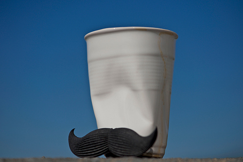 a dented white plastic cup with a fake black mustache stuck to the front. the backdrop is blue sky.