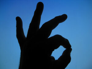 a blue background with a black hand over it making the okay sign