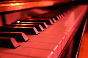 a close up of piano keys, bathed in red light