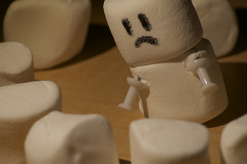 a very sad looking character made of marshmallows. they have little hands made from white thumbtacks.