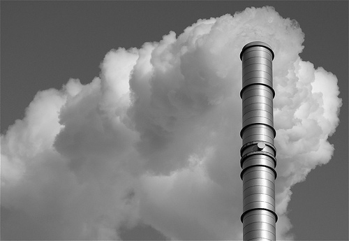 a black and white photo of a smokestack pouring out a thick cloud of smoke