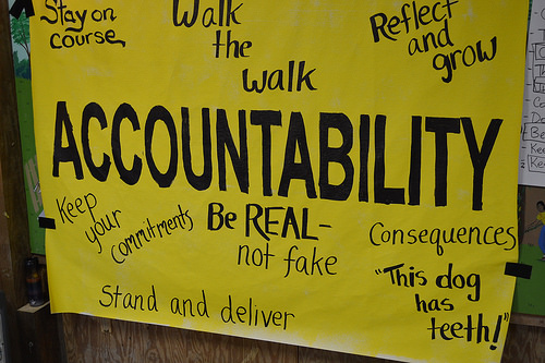 "It's a yellow poster board paper. In the center in large letters is the word ""Accountability."" It also says (moving from top left and moving clockwise): ""stay on course,"" ""walk the walk,"" ""reflect and grow,"" ""consequences,"" ""This dog has teeth!"" ""be real - not fake,"" ""stand and deliver,"" and ""keep your commitments"""