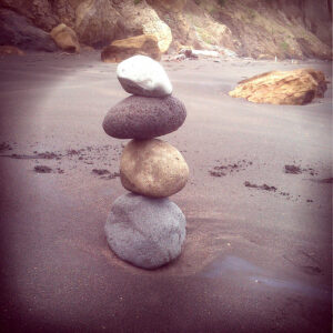 4 stones of different sizes, delicately balanced, on a beach