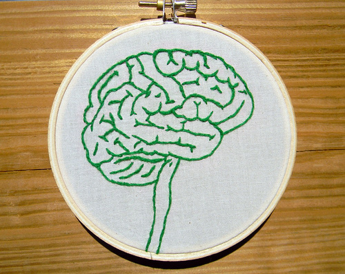 a small green brain embroidered on a circular canvas, sitting on a wooden table
