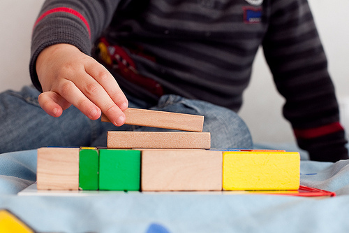 a small child wearing a striped shirt is playing with building blocks
