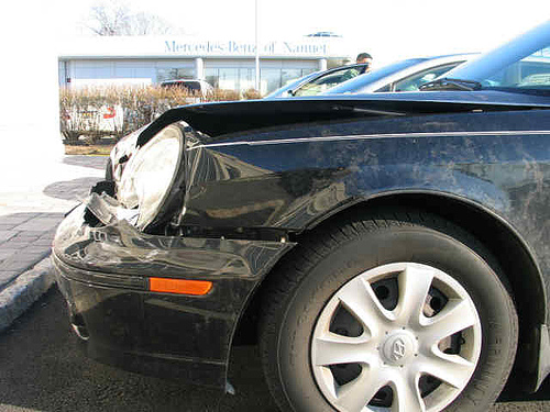 The front end of a black car, driver's side. It has clearly been involved in an accident. The crumple zone (the nose of the car) is all banged up.
