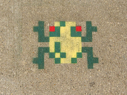 a sidewalk painting of a pixellated frog (in the style of the main character icon for the arcade game Frogger)
