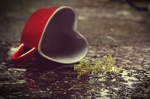 A red ceramic heart-shaped mug tipped on its side on the ground. It appears to have spilled out some mossy substance next to it.