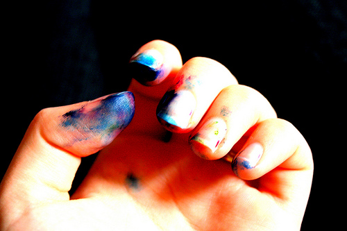 a hand with bluish-people ink stains on the fingers