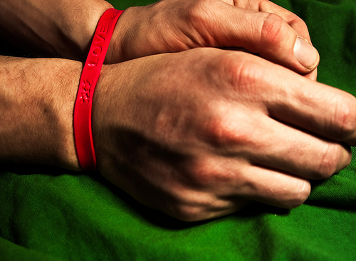 "a picture of 2 hands restrained by a red rubber bracelet that says ""LOVE"" on it"