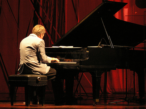A person with short sandy hair viewed from behind. They are sitting at a grand piano playing. There's a dark red curtain in the background