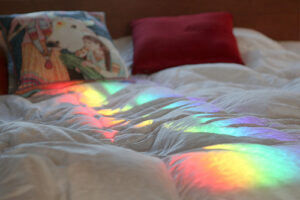 A bed with a white comforter and two pillows. The left pillow has a scene of what looks like a young girl and a horse printed on it. The right pillow is burgundy colored. There's a patch of rainbow light streaming across the middle of the bed.