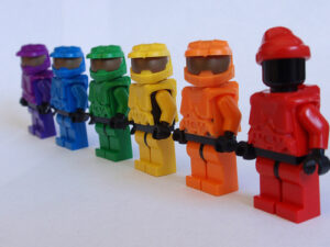 Lego people, arranged, in a rainbow color formation. The closest Lego person is red, next closest is orange, next yellow, green, blue, and purple (as you get further away from the camera)