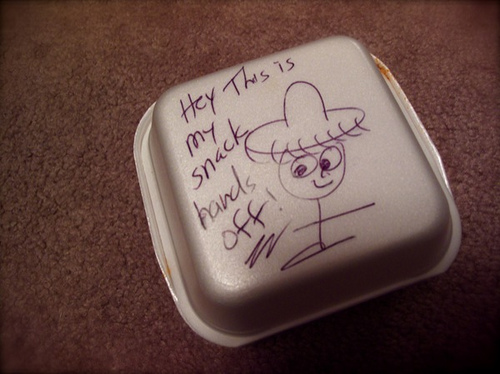 "A styrofoam box container for takeout leftovers. It's closed. Someone has written on it in pen: Hey this is my snack. Hands off!"" and drawn a little stick person wearing a fringed hat."