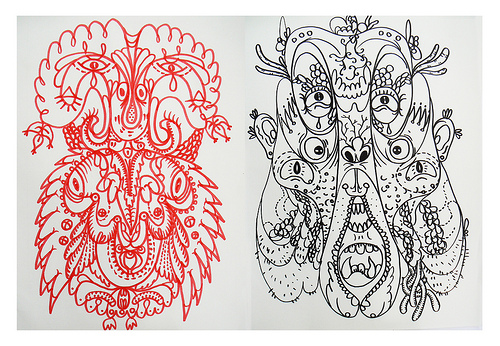 A drawing of the faces of 2 twin demons. The one on the left is drawn in red ink. The one on the right is drawn in black.