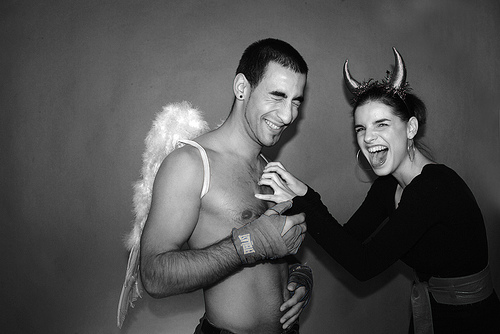 two people, the one on the left has short hair and is wearing angel's wings and is smiling with their eyes closed. The one on the right is wearing devil horns and appears to be tickling the other person's chest and has an open-mouthed expression.