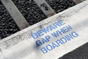 "a concrete train platform. It has the following stamped on it in blue letters ""BEWARE GAP WHEN BOARDING"""