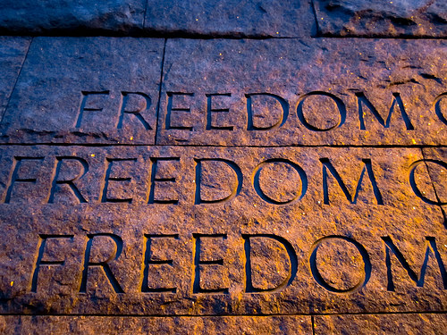 "a closeup of the Roosevelt Memorial. Stone that has the words ""FREEDOM"" carved 3 times"