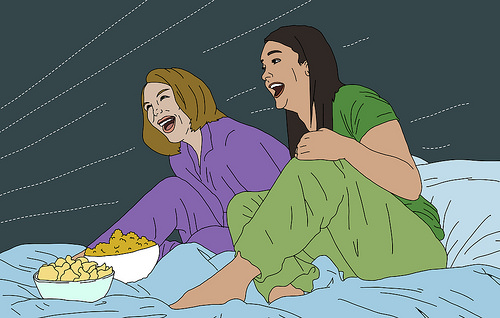 Two friends sitting on a bed watching TV together. They are laughing. There are also 2 bowls of popcorn on the bed.