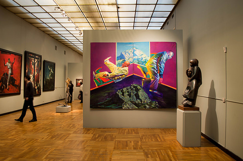 a photo of an art gallery, to the left is a bronze statue that appears to be a woman with a child on her shoulders. Directly ahead is a brightly colored painting that appears to be a man leaping out of his own body. Off to the right, there appears to be a triptrych of modern images of the crucifixion. There are a few nondescript/blurry patrons and distantly in the photo there is a painting, details unclear, but it appears to be a portrait of someone wearing a red outfit.