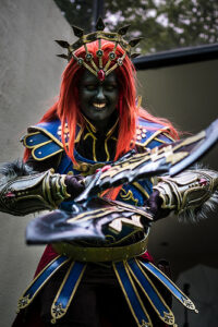 a cosplay of Ganon from the legend of Zelda. Ganon has a blackened face, a bright red hair, is wearing armor of navy and gold, and is holding out 2 crossed (thick) swords in front of them
