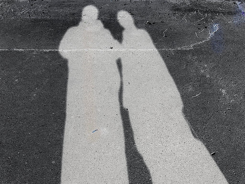 the lighter grey outline of 2 human figures on a darker gray background, they look kind of like ghost people