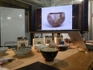 a workshop for kintsugi, the Japanese art of repairing pots by adorning them with gold sealant, making the flaws more beautiful. In the back center is a screen with a gilded pot, off to the left is a dry erase board. The foreground has a table covered with a bunch of pots in various states of repair as well as electronic devices that are ostensibly used in repairing the pots