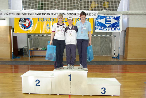 3 people wearing medals standing on a winners' podium. Instead of standing in ranked places, first, second, and third, all 3 winners are standing atop the #1 platform