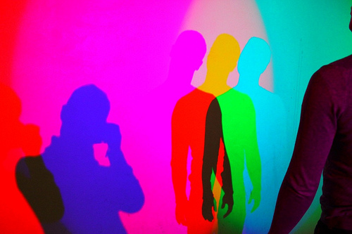 a bunch of multicolored silhouettes of people superimposed on a pinkish (though multicolored) background
