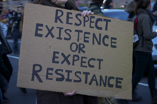 "a brown sign cardboard sign that reads ""respect existence or expect resistance"""