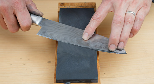 a pair of hands sharpening a knife on a sharpening block