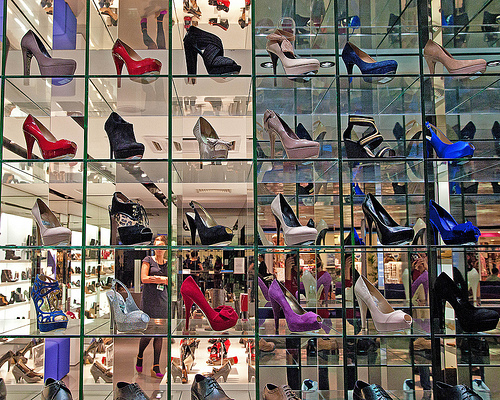 a variety of shoes displayed in a transparent glass cube. Behind the display can be seen the background image of shoppers browsing in a shoe store