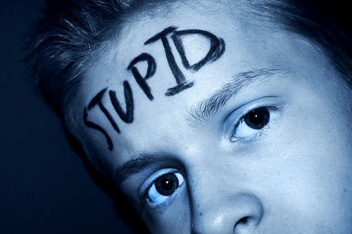 "a person with a sad look in their eyes that has the word ""stupid"" written across their forehead"