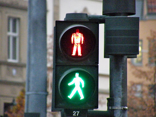 "A stoplight for pedestrians that has both the ""green walking person"" and ""red stopped person"" lit, sending a message of ambiguity."