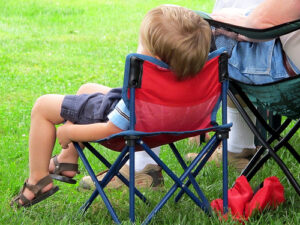 a very bored looking small child sitting in camping chair, viewed from behind