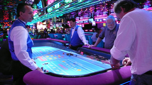 a craps table in a casino. Two dealers stand next to the table on opposite sides. There are appear to be two customers off to the right of the frame.