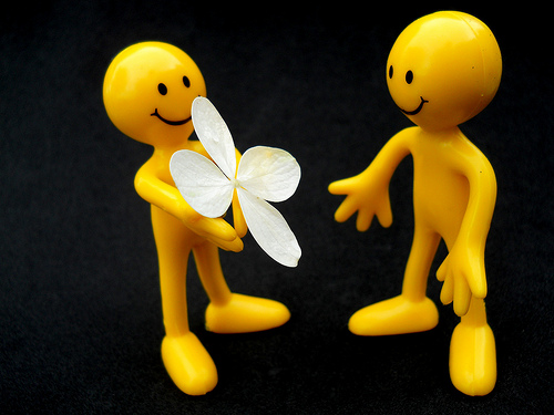 two yellow stick figure sculptures. They are both smiling. The one on the left seems to be giving a white flower petal to the one on the right.
