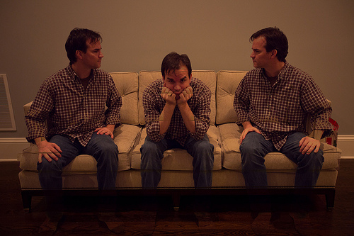 3 people sitting on a couch (it appears to all be the same person). They are wearing the same plaid shirt and blue jeans. The ones on the left and right and facing each other, with a tense expression on their faces. The person in the middle is hunched down, facing forward with their head in their hands.