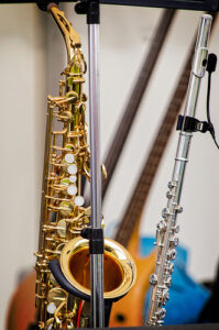 a picture of a saxophone and a flute, propped up on music stands